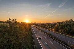 The road traffic on a motorway at sunset.  stock photo