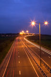 Road and Traffic at Night. Road at night with traffic trails and street lamps Royalty Free Stock Photography
