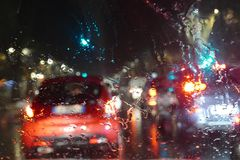 Road traffic in rainy night with cars and lights selective focus on rain drops blur effect Royalty Free Stock Image