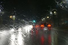 Road traffic in rainy night with cars and lights selective focus on rain drops blur effect Stock Photo