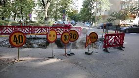 Road traffic warning signs and a plastic fence around a big hole in the asphalt from where steam comes out.  stock footage