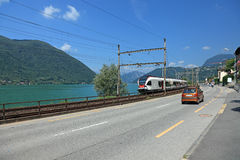 Road and train along swiss Lake. Stock Image