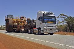 Road Train, With Flat Top Trailer, Carring a Semi Dismantled Iron Ore Carrier. stock photography
