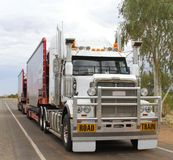 Road train is transporting consumer goods in the Outback, Australia. A road train in the countryside of the Outback, Australia. Road trains are allowed a maximum Royalty Free Stock Image