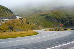 Road Transfegerash. Serpentine road in the mountains of Romania. Pass Transfegerash. The road in the fog and a sign Stock Image