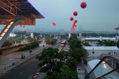 Road with transport, footpaths, palm trees, white tents. Modern big city. Red gel balls in the air. Guangzhou Exhibition Center stock photography