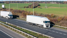 Road transport - lorries on the british motorway. Two lorries in motion on the british motorway stock image