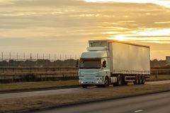 Road transport, Lorry on the road. Articulated lorry in motion on the road during beautiful sunset royalty free stock image