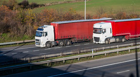 Road transport - two lorries on the motorway. Two lorries with red trailers driving side to side on the motorway royalty free stock image