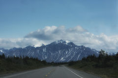The Road Less Traveled. Snowy mountain range photographed while traveling the ALCAN, Alaska Canadian Highway Royalty Free Stock Images