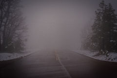The road less traveled. Two lane highway after a fresh spring snow storm Royalty Free Stock Photos