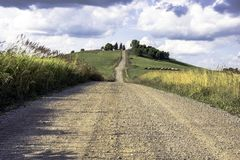 The Road Less Traveled. View of a gravel road in the center of the frame, leading up a hill with dramatic cloudscape Royalty Free Stock Photography