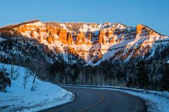 Free Road Traveling Toward Desert Sandstone Formations Under Golden Sunset Alpenglow Stock Image - 168824601