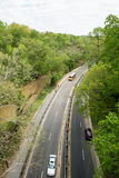 Road between tree. Along the creek with cars and a school bus running through Royalty Free Stock Images
