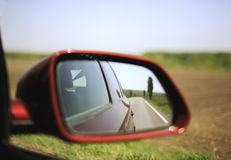 Road and trees reflected in rear-view mirror Royalty Free Stock Photos