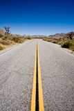 Road trip. Through joshua tree national park, california. straight stretch of road with blue sky and copyspace Stock Photography