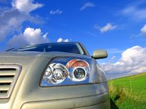 Road trip. Car with greenery on the clouds and blue sky Stock Photos