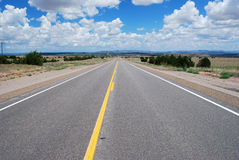 Road trip. Long asphalt road with a cloudy sky Stock Image