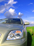 Road trip. Car with greenery on the clouds and blue sky Stock Image