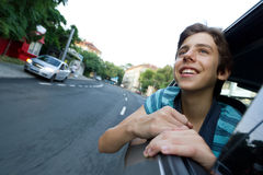 Excited Boy in car road trip. Smiling and excited male teenager on a road trip looking out of a car window Stock Photography