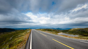 Road trip. A road over mountain top with a moody sky Stock Photo