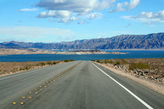 Road Trip. Paved road leading into a lake Stock Photo