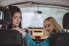 Road trip. Beautiful young girls having road trip in minivan together Royalty Free Stock Photos