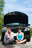 Road Trip - Car Broke Down. A young couple sits dejectedly as their car breaks down Stock Photo