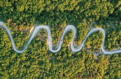Road trip, car going through a curve road. Aerial point of view stock photo