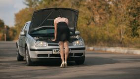 Back of a womam trying to repair a car