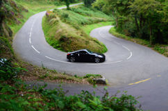 Road trip car on windy road. Nissan 350z  sports car on a windy road miniature car Stock Image