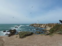 Coastal Cliff Area with Lighthouse and Birds Flying in the Sky stock image