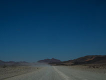 Road trip through dusty unpaved road among desert and mountain l. Andscape with clear blue sky Royalty Free Stock Images