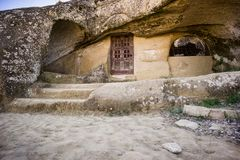 Cave house with old wood door stock photography