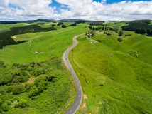 Road trip on rolling hill in Rotorua, New Zealand. Road trip on the hill with green grass and sheep farm meadow in Rotorua, New Zealand North Island from aerial Royalty Free Stock Photo