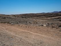 Road trip through rough dusty unpaved road with vehicle tyre tra Royalty Free Stock Images