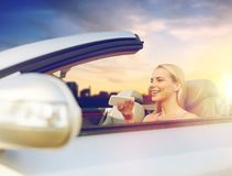 Woman recording voice on smartphone at car. Road trip, technology and communication concept - happy young woman calling on smartphone or using voice command royalty free stock photos