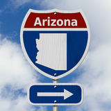 Road trip to Arizona. Red, white and blue interstate highway road sign with word Arizona and map of Arizona with sky background royalty free stock photo