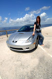 Road trip to beach. A happy young woman in jeans and t-shirt standing next to her car parked at the beach royalty free stock image