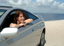 Road trip to beach. A happy young woman sitting in her car parked at the beach royalty free stock images