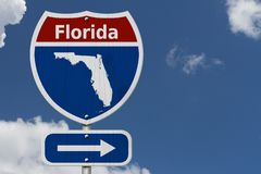 Road trip to Florida with sky. Road trip to Florida, Red, white and blue interstate highway road sign with word Florida and map of Florida with sky background royalty free stock photo