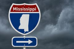 Road trip to Mississippi with stormy sky. Road trip to Mississippi, Red, white and blue interstate highway road sign with word Mississippi and map of Mississippi stock image