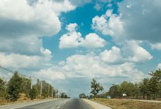 Road trip to out of town with lines of green trees and nice clouds blue sky in summer Stock Image