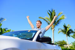 Road trip travel - free man driving car in freedom. Happy young adult cheering in convertible for his summer vacations Stock Images