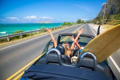 Hawaii road trip. Road trip travel - girls driving car in freedom. Happy young girls cheering in convertible car on summer Hawaii vacations stock photos