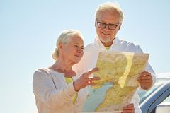 Senior couple at car looking for location on map Stock Images