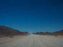 Road trip through unpaved road among desert and mountain landsca Stock Photo