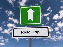 Road trip. White highway style sign board with text 'Road Trip' in black letters and above it a bold white arrow on a green sign, background of blue sky and Stock Photography