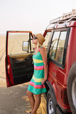 Road tripping is all about freedom. Shot of young female traveler in hat and sunglasses standing near car on the beach Royalty Free Stock Photos