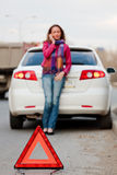 Road trouble. Woman calls to a service standing by a white car. Focus is on the red triangle sign. Evening light Royalty Free Stock Images